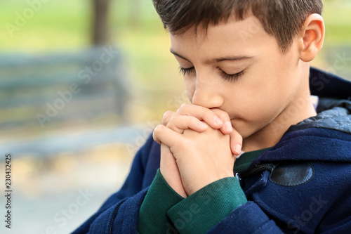 Leinwanddruck Bild Little boy praying outdoors