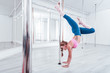 Stand near pole. Dark-haired strong and healthy woman wearing sportswear doing head stand near pole