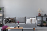 Industrial living room with simple grey sofa and metal furniture, real photo with copy space on the wall