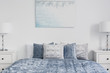Poster above blue bed with pillows in white simple bedroom interior with lamps on cabinets. Real photo