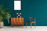 Mockup poster on pine green wall in scandinavian minimal interior with retro furniture and plant, real photo - 230439076