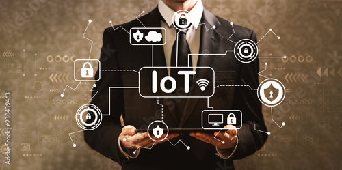 IoT security theme with businessman holding a tablet computer on a dark vintage background © Tierney