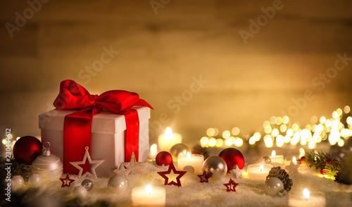 Weihnachten Hintergrund mit Geschenk und rotem Band, Kerzen, Lichterkette, Weihnachtsdeko und Schnee - 230444612