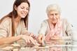 Leinwanddruck Bild - Enkeltochter spielt Domino mit Großmutter