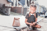 Gathering chestnuts. Cute dark-haired schoolgirl gathering chestnuts in the street on the way home - 230446491