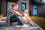 On the porch. Handsome blonde-haired father sitting on the porch near his cute little girl wearing white dress - 230447690