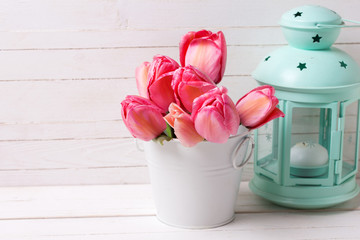 Fresh pink tulip flowers in white color bucket and decorative mint lantern on wooden background.