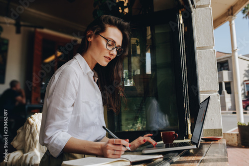 Foto Murales Businesswoman working from a coffee shop