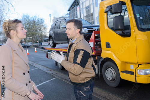 Leinwanddruck Bild car towing worker talking to customer
