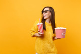 Joyful young woman in 3d imax glasses looking aside watching movie film hold bucket of popcorn, plastic cup of cola or soda isolated on yellow background. People sincere emotions in cinema, lifestyle. - 230463277