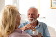 Old man and woman drinking coffee at home