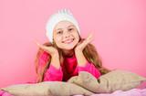 Winter season coziness attribute. Winter season concept. Winter fashion accessory. Kid girl knitted hat. Winter accessory concept. Girl long hair dream pink background. Kid dreamy lean on pillows - 230466280