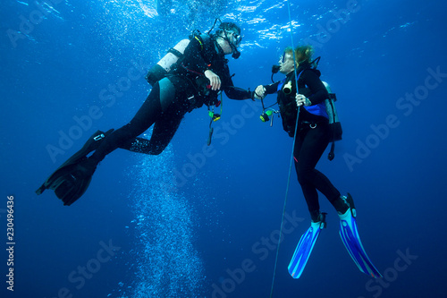 Leinwanddruck Bild Happy couple scuba divers  hovering together on a safety stop