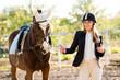 Leinwanddruck Bild - Girl equestrian rider stands near the horse. Horse farm