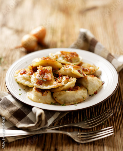 Fried dumplings stuffed with cabbage and meat sprinkled with bacon greaves and chopped parsley on a white plate on a wooden rustic table. - 230526625