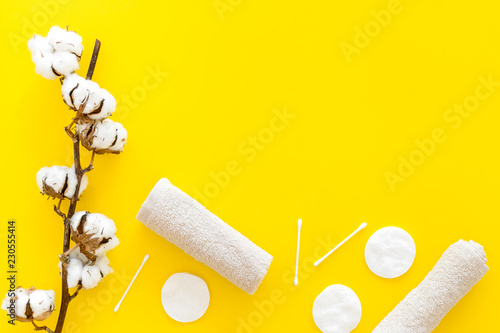 Leinwanddruck Bild Products made of cotton. Bath accessories. Towels, cotton pads and swabs near dry cotton flowers on yellow background top view copy space