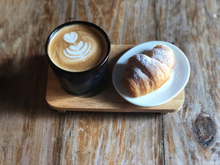 Delicious Breakfast;  Heart love Latte art coffee in Black cup and Croissant topped with icing sugar in white dish on the wooden try and vintage wooden table.