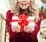 Christmas gift in female hands on shopping mall background - 230569401
