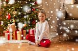 christmas, holidays and childhood concept - smiling girl at home - 230572051