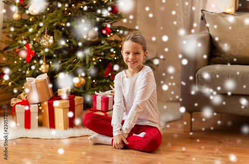 christmas, holidays and childhood concept - smiling girl at home
