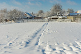 Winter landscape with pedestrian path through snow covered field - 230580817