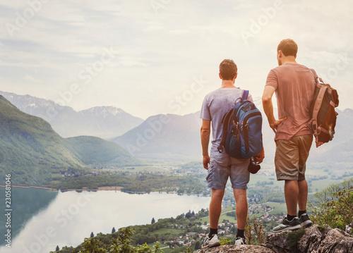 ludzie podróżujący, wędrowcy stojący na szczycie góry i relaksujący z plecakami