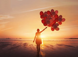 follow your dream, inspiration concept, silhouette of woman with colorful balloons on the beach - 230581467