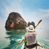 travel by kayak in Asia, beach holiday tourism activity, man tourist kayaking on tropical beach - 230581474