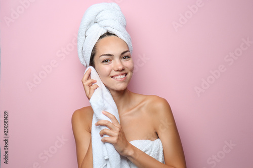 Leinwanddruck Bild Beautiful young woman with towel wiping skin after shower on color background