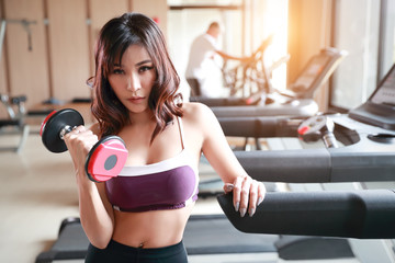 fitness girl lifting dumbbell and workout in gym © Parkpoom