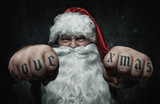 Funny mad Santa Claus showing fists with tattoos