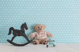 Old wooden toy horse rocking chair, teddy bear and blue vintage motorcycle in baby's room - 230597861