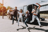 Excited Young People Jumping in front of Tour Bus