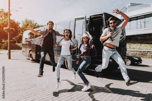 Foto Murales Excited Young People Jumping in front of Tour Bus
