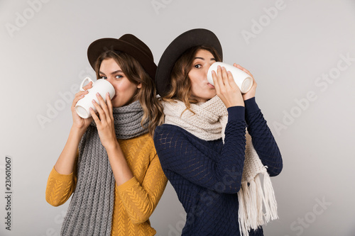 Leinwanddruck Bild Image of two brunette women wearing hats and scarfs drinking hot tea from cups isolated over gray background
