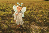 Little girl in a butterfly costume with wings in the field