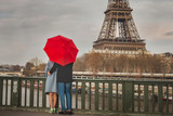 autumn in Paris, couple under red umbrella near Eiffel tower, fall season, love in rainy day, romantic moment on the bridge - 230617464