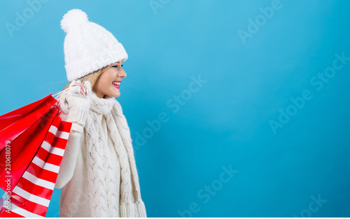 Leinwanddruck Bild Happy young woman holding shopping bags on a blue background