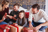 Happy children opening christmas present with parents - 230628857