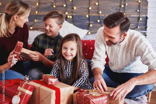 Leinwanddruck Bild Happy children opening christmas present with parents