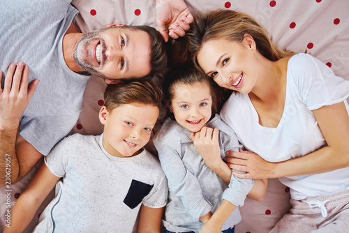 Portrait of happy family lying on the bed