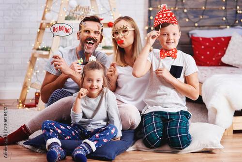 Leinwanddruck Bild Portrait of happy family with christmas mask