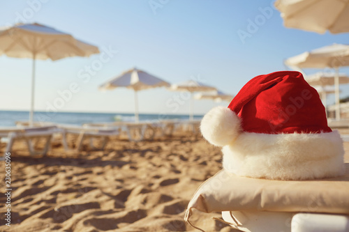 Foto Murales Santa Claus hat on the beach on Christmas Day. The concept of Christmas by the sea.
