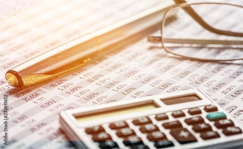 Kalkulator, długopis, okulary i raport finansowy. Ścieśniać