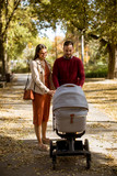 Happy young parents walking in the park and driving a baby in baby carriage - 230654845