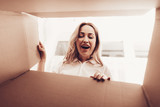 Smiling Woman Looks into Empty Box from Inside. - 230656045