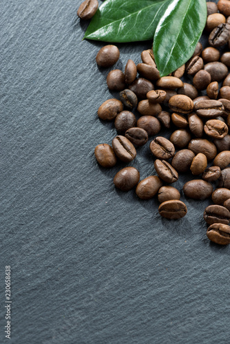 coffee beans and leaves on a dark background, space for text, vertical