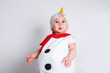 Leinwandbild Motiv Merry Christmas and Happy New Year. Happy baby girl in snowman costume on white background