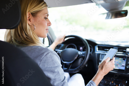 Poster Beautiful young woman using her mobile phone in the car.