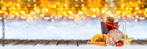 Glühwein lebkuchen und weihnachten dekoration auf schnee vor bokeh lichterhintergrund / hot spiced wine on christmas xmas market snow bokeh background with many lights ice blue snow